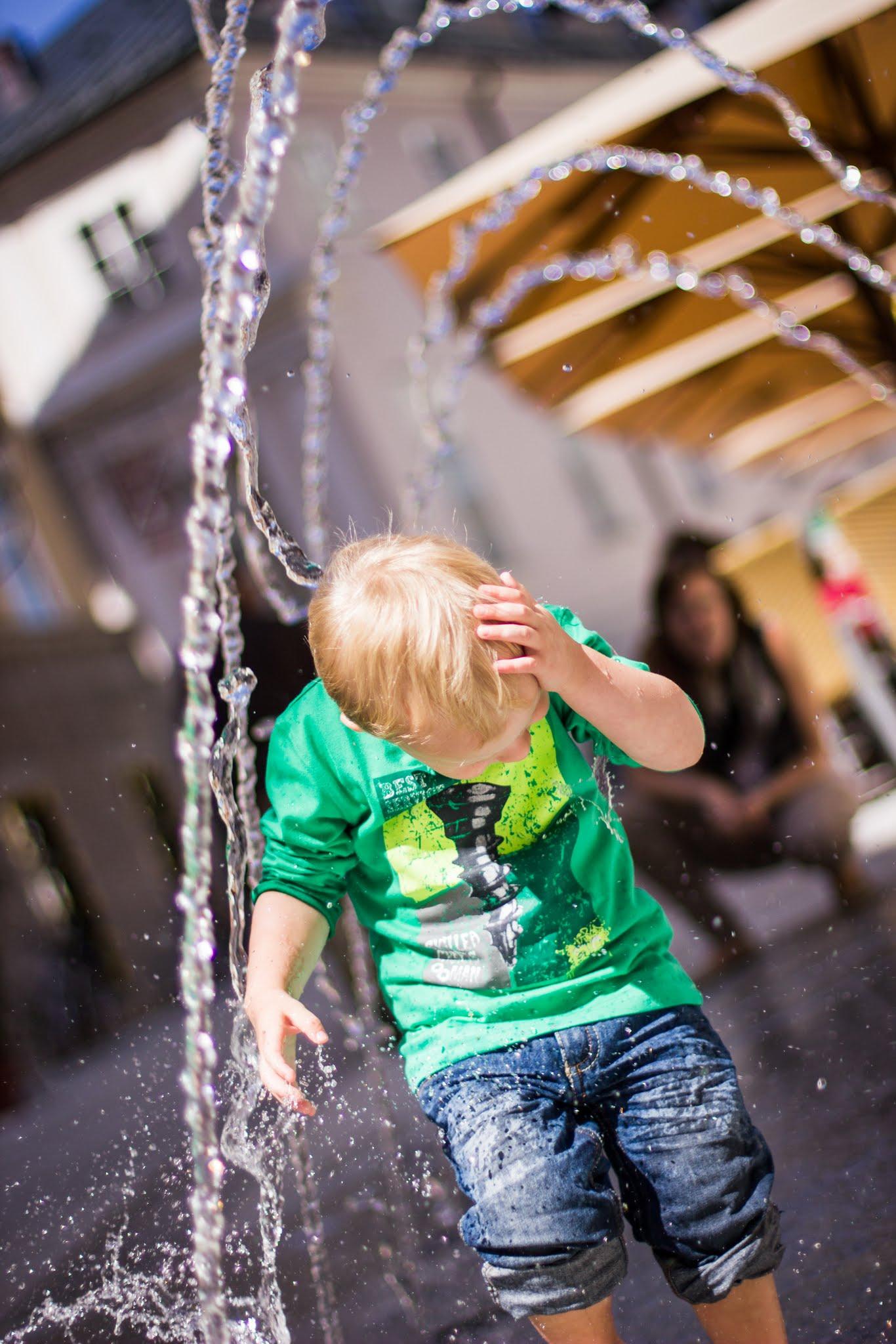 Voll bekleideter Junge steht kurz vor Kollision mit einem Wasserstrahl